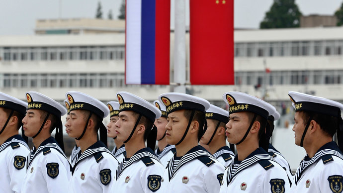 "Chinese sailors stand in formation in front of national flags of Russia (L) and China, as they get ready for a welcoming ceremony for Russian naval vessels ahead of the ""Joint Sea-2014"" naval drill, at a port in Shanghai, May 18, 2014.(Reuters / China Daily)"