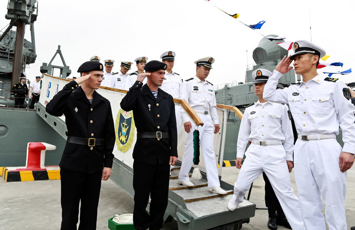 "Russian sailors (L) salute to Chinese sailors as they visit Russian guided missile cruiser Varyag ahead of the ""Joint Sea-2014"" naval drill, at a port in Shanghai, May 19, 2014.(Reuters / China Daily)"