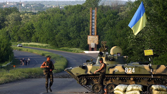 Ukrainian army servicemen stand near an armoured fighting vehicle as they man a checkpoint in the outskirts of Slaviansk (Reuters / Yannis Behrakis)