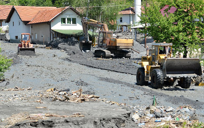 Workers use a backhoe and bulldozers to clear the earth after a landslide in the flooded village of Topcic Polje, near the northern Bosnian city of Doboj, on May 19, 2014 (AFP Photo / Elvis Barukcic)