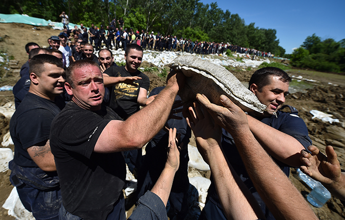 Volunteers and police officers pass sandbags to reinforce the bank of the river Sava near Sabac, 100 kilometres west of Belgrade, on May 19, 2014. (AFP Photo / Andrej Isakovic)