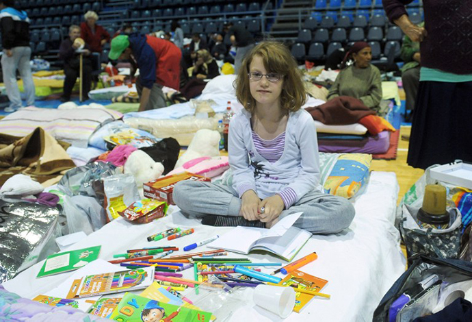 A girl sits on a matress with coloured felt pens and books in a collective centre for people evacuated from the flooded town of Obrenovac on May 19, 2014 in Obrenovac, some 30km southwest of Belgrade. (AFP Photo / Alexa Stankovic)