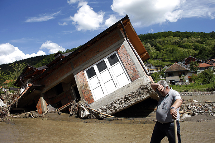A man reacts near a house tilted by floods in the village of Krupanj, west from Belgrade, May 19, 2014. (Reuters / Marko Djurica)