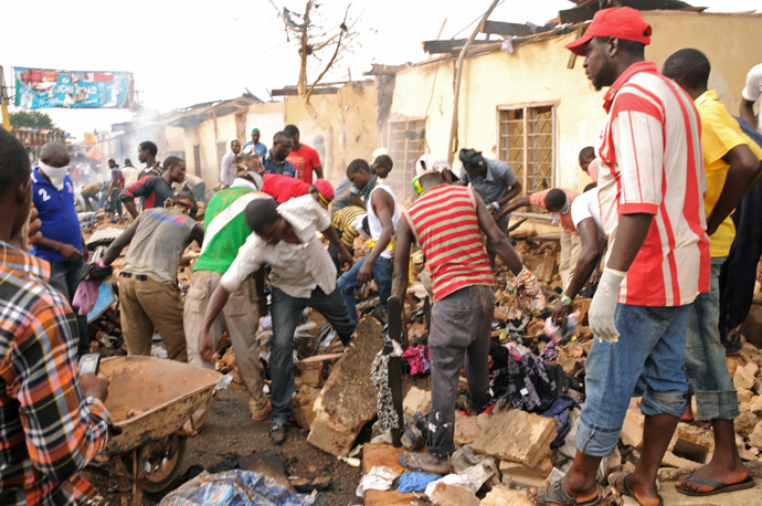 Stallkeepers salvage their belongings as rescuers and residents gather at the charred scene following a bomb blast at Terminus market in the central city of Jos on May 20, 2014 (AFP Photo / STR)