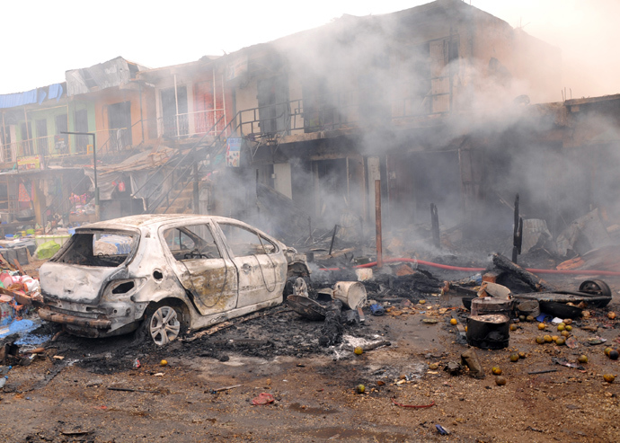 The wreckage of a burnt vehicle remains in front of burning shops following a bomb blast at Terminus market in the central city of Jos on May 20, 2014 (AFP Photo / STR)