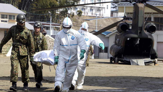 A person, who is believed to be have been contaminated with radiation, in a white bag is carried by soldiers at a radiation treatment centre in Nihonmatsu city in Fukushima prefecture on March 13, 2011. (AFP Photo)