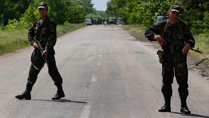 Ukrainian soldiers block traffic near the site (seen in background) where Ukrainian servicemen were killed on the outskirts of the eastern Ukrainian town of Volnovakha, south of Donetsk May 22, 2014.(Reuters / Yannis Behrakis )