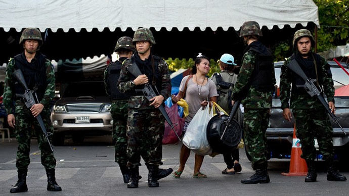 A Thai anti-government protester (C) leaves the main camp-site near the Government House in Bangkok on May 23, 2014 a day after Thai military seized power. (AFP Photo / Manan Vatsyayana)