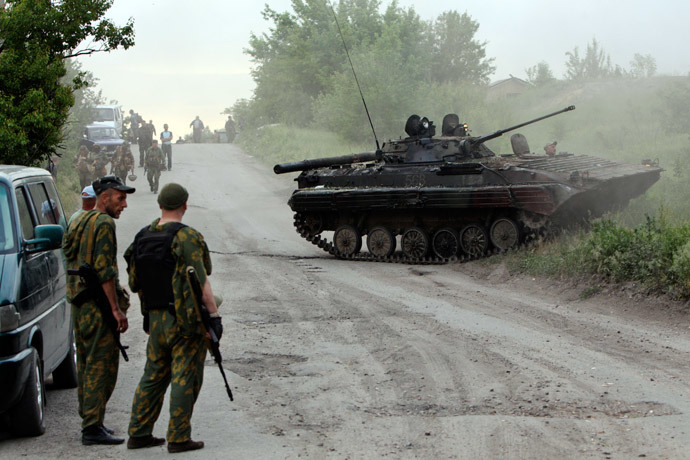 Pro-Russian activists stand near an armoured fighting vehicle (AFV) that they said was captured from the Ukrainian army during a fight outside the eastern Ukrainian town of Lysychansk May 22, 2014.(Reuters / Valentyn Ogirenko)