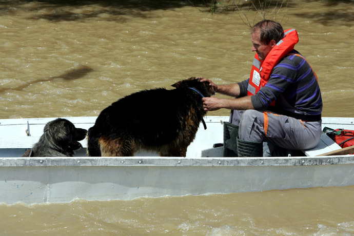 A Croatian rescuer with two dogs in a boat on a flooded street in the village of Gunja, in eastern Croatia, 18 May, 2014. (AFP Photo)