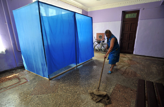 A members of the election comission mops the floor of a pooling station ahead of the upcoming Ukrainian presidential election at the Octyabr village in the Donetsk region on May 22, 2014. (AFP Photo/Genya Savilov)