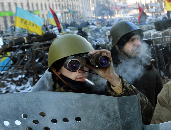 A man uses binoculars as protesters guard a road block in central Kiev on January 31, 2014. (AFP Photo / Sergei Supinski)