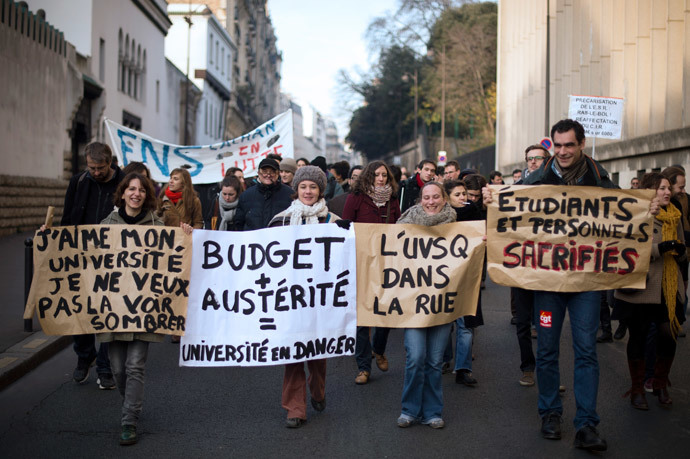 French protesters, including university students and researchers, hold banners as they rally against budget austerity in the education field. (AFP Photo / Lionel Bonaventure)