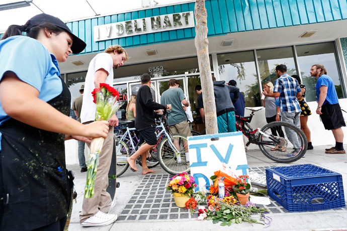 A woman places a flowers at a makeshift shrine outside a deli that was one of nine crime scenes after series of drive-by shootings that left 7 people dead in the Isla Vista section of Santa Barbara May 24, 2014. (Reuters / Jonathan Alcorn)