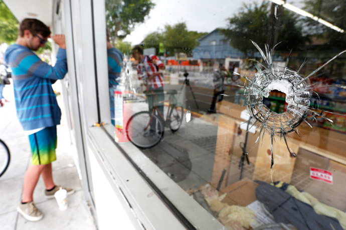 A man looks through a window with bullet holes at a deli that was one of nine crime scenes after series of drive -by shootings that left 7 people dead in the Isla Vista section of Santa Barbara May 24, 2014. (Reuters / Jonathan Alcorn)