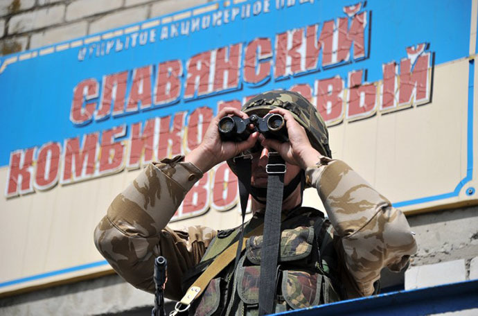 A Ukrainian army soldier looks through binoculars as he stands guard at a checkpoint outside of Slavyansk, on May 25, 2014. (AFP Photo / Genya Savilov)