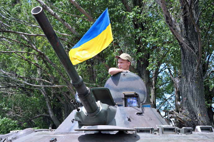 A Ukrainian soldier stands guard next to an Armoured Personnel Carriers (APC) as a flag of Ukraine floats in the background, on the road from Izyum to Slavyansk on May 20, 2014. (AFP Photo)