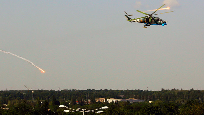 A Ukrainian helicopter Mi-24 gunship fires decoy flares over a residential area moments after attacking Donetsk international airport May 26, 2014. (Reuters / Yannis Behrakis)