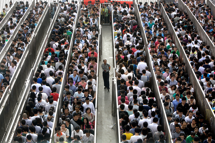 A security officer stands guard as passengers line up and wait for a security check during morning rush hour at Tiantongyuan North Station in Beijing May 27, 2014 (Reuters / Jason Lee)
