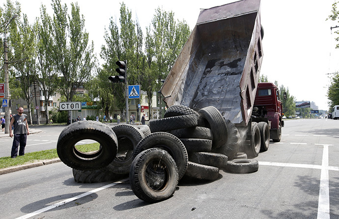 A truck unloads tyres as supporters of the self-proclaimed Donetsk People's Republic erect a barricade on a road which leads to an airport in the eastern Ukrainian city of Donetsk, May 28, 2014. (Reuters / Maxim Zmeyev)