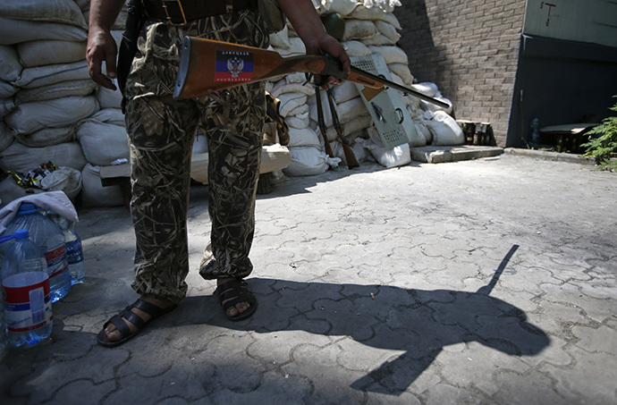 An armed supporter of the self-proclaimed Donetsk People's Republic stands guard at a newly erected barricade on a road which leads to an airport in the eastern Ukrainian city of Donetsk May 28, 2014. (Reuters / Maxim Zmeyev)