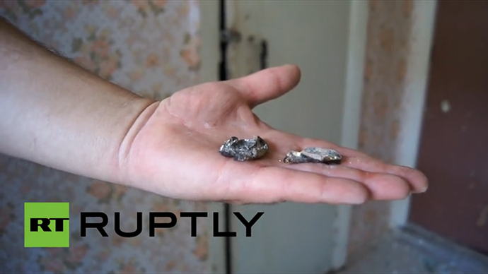 A woman working at Slavyansk school no.13 shows shrapnel of the shell that hit the school's roof on May 28, 2014. (A screenshot from Ruptly video)
