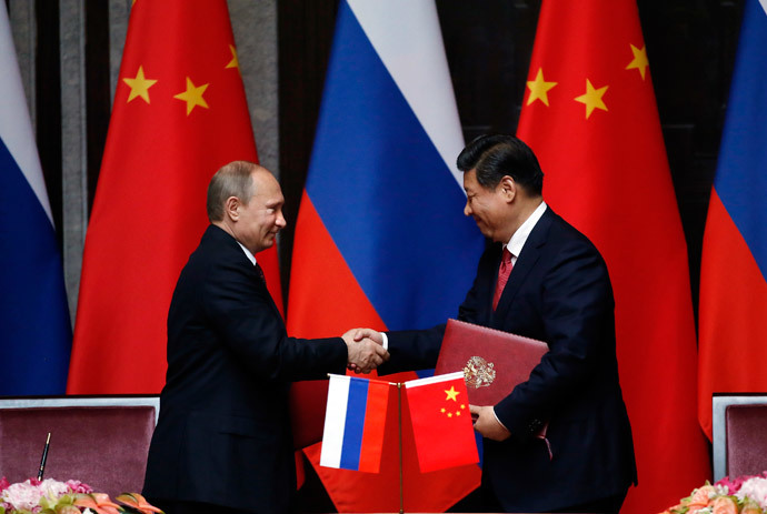 Russia's President Vladimir Putin (L) and China's President Xi Jinping shake hands after signing an agreement during a bilateral meeting at the Xijiao State Guesthouse ahead of the fourth Conference on Interaction and Confidence Building Measures in Asia (CICA) summit, in Shanghai on May 20, 2014.( AFP Photo / Carlos Barria)