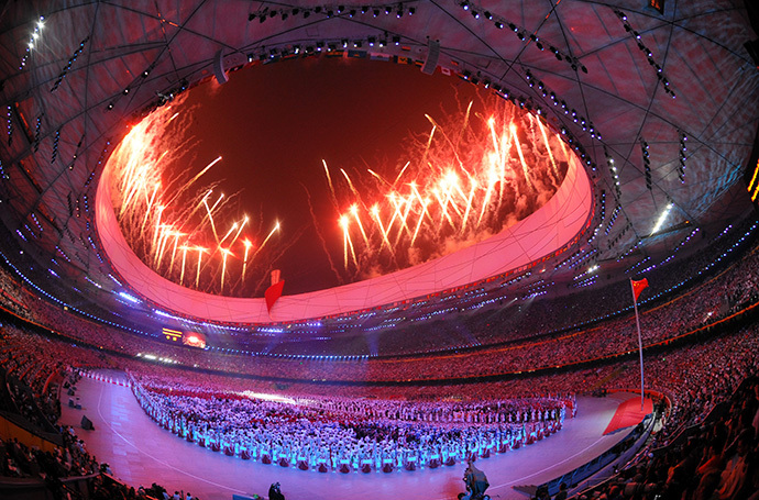 Delegations gather at the centre of the stadium as fireworks light up the sky during the opening ceremony of the 2008 Beijing Olympic Games in Beijing on August 8, 2008. (AFP Photo / Joe Klamar)