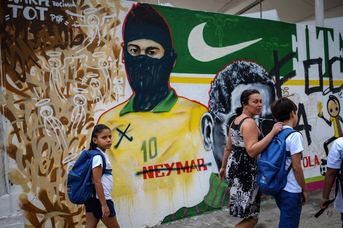 People walk past a vandalized graffiti depicting Brazilian national footballer Neymar with a hood used by members of the anarchist group known as Black Bloc which is against of the FIFA World Cup Brazil 2014 football tournament, in Rio de Janeiro, Brazil, on May 27, 2014. (AFP Photo / Yasuyoshi Chiba)
