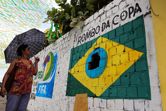 A pedestrian looks at a graffiti in protest against the 2014 World Cup that shows the Brazilian flag painted around a hole in a wall in Manaus, one of the host cities, May 23, 2014. (Reuters / Bruno Kelly)