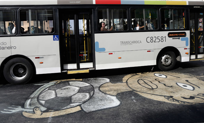 A public bus drives over a graffiti referencing the 2014 World Cup in Rio de Janeiro May 22, 2014. (Reuters / Ricardo Moraes)