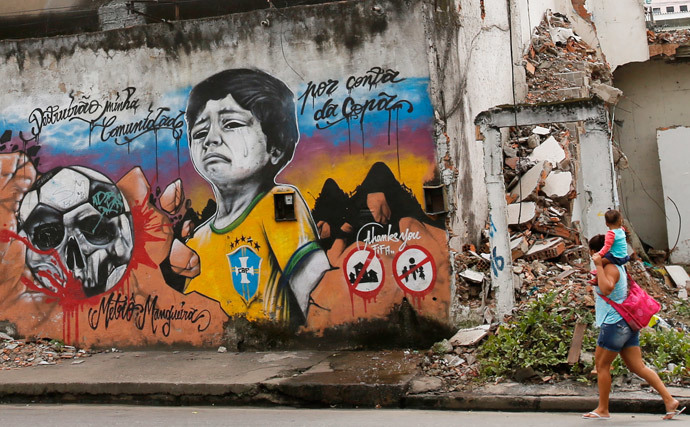 A woman walks with her child on her shoulders in front of graffiti against the infrastructure work for the 2014 World Cup at the Metro Mangueira slum near the Maracana Stadium in Rio de Janeiro April 10, 2013. (Reuters / Sergio Moraes)