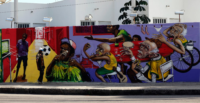 A man walks past by graffiti painted on the a wall in reference to the 2014 World Cup in Rio de Janeiro May 14, 2014. (Reuters / Sergio Moraes)