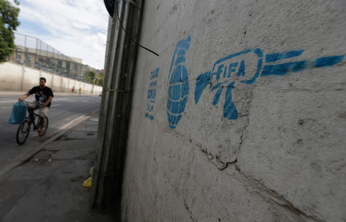 A man rides his bike past a graffiti referencing the 2014 World Cup in Rio de Janeiro May 23, 2014. (Reuters / Ricardo Moraes)