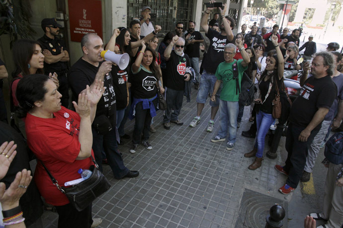 A protester delivers a speech through a megaphone during a demonstration outside the central employment office in Valencia, April 30, 2014. (Reuters/Heino Kali)