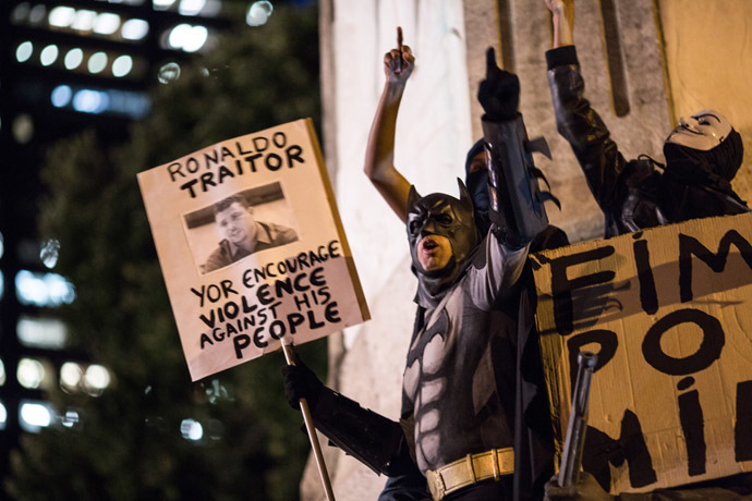 A man fancy-dressed as American comic hero Batman shouts slogans during a protest by anarchist group Black Bloc against the FIFA World Cup in Rio de Janeiro, Brazil, on May 30, 2014 (AFP Photo/YASUYOSHI CHIBA)