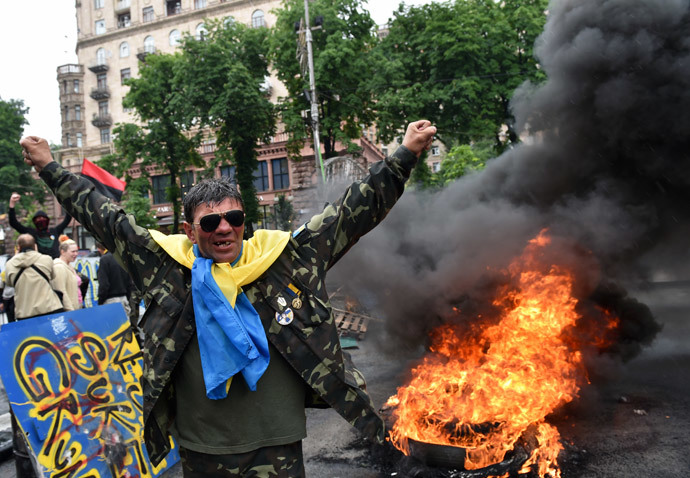 "A protester from Kiev's Independence Square, the so-called ""Maidan"", gestures as fellow protesters burn tyres to protect their barricades from being dismantled by communal services on May 31, 2014 in the centre of Kiev.(AFP Photo / Sergei Supinsky )"