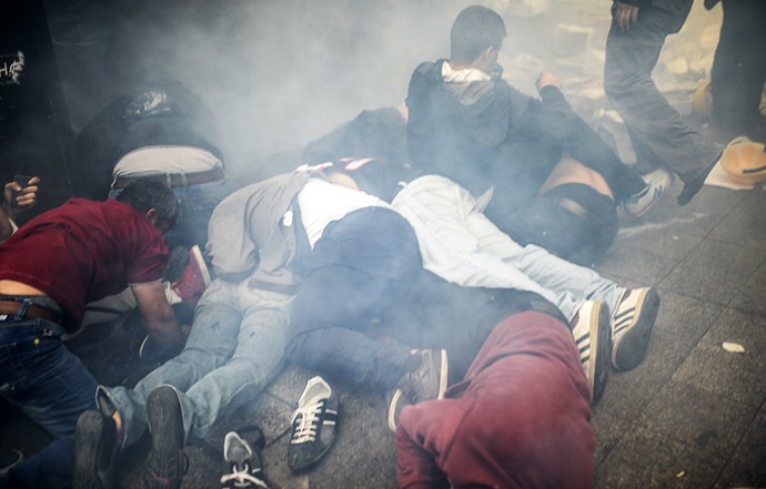 Injured protesters lie on the ground as Turkish riot police officers fire tear gas to disperse demonstrators gathered on the central Istoklal avenue near Taksim square in Istanbul, on May 31, 2014, as the police blocked access to the square during the one year anniversary of the Gezi park and Taksim square demonstrations. (AFP Photo/Bulent Kilic)