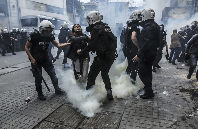 Turkish riot police officers hold up a protester seriously affected by tear gas as police officers use tear gas to disperse protesters who gathered on the central Istoklal avenue near Taksim square in Istanbul, on May 31, 2014, as the police blocked access to the square during the one year anniversary of the Gezi park and Taksim square demonstrations (AFP Photo/GURCAN OZTURK)