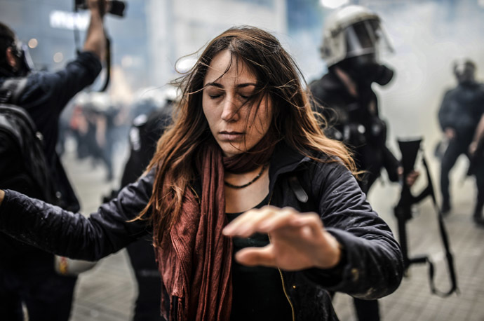 A protester walks away with closed eyes as Turkish riot police officers fire tear gas to disperse demonstrators gathered on the central Istoklal avenue near Taksim square in Istanbul, on May 31, 2014, as the police blocked access to the square during the one year anniversary of the Gezi park and Taksim square demonstrations. (AFP Photo/Bulent Kilic)