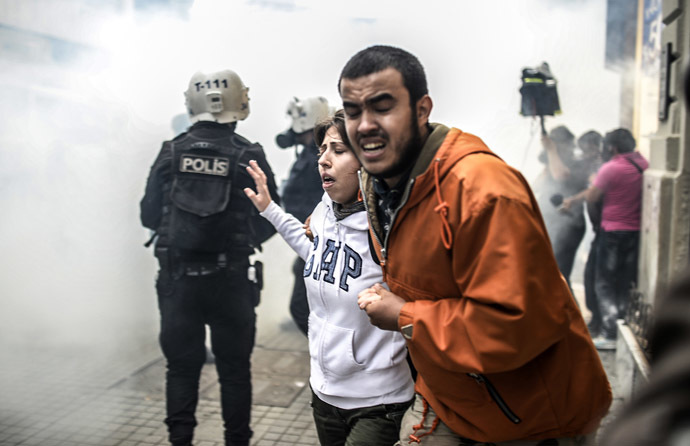 Protesters run away as Turkish riot police officers fire tear gas to disperse demonstrators gathered on the central Istoklal avenue near Taksim square in Istanbul, on May 31, 2014, as the police blocked access to the square during the one year anniversary of the Gezi park and Taksim square demonstrations. (AFP Photo/Bulent Kilic)