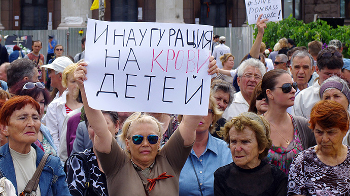 "A woman holds a sign reading ""Inauguration by the blood of children"" during a rally held by pro-Russian activists marking International Day for Protection of Children in the southern Ukrainian city of Odessa on June 1, 2014. (AFP Photo / Alexey Kravtsov)"