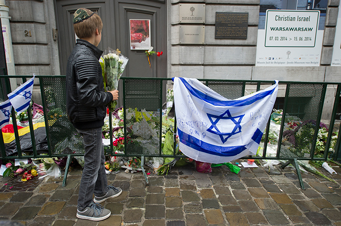 A Jewish boy stands with flowers in front of an Israeli flag and flowers laid in front of the Jewish Museum in Brussels on May 26, 2014 (AFP Photo)