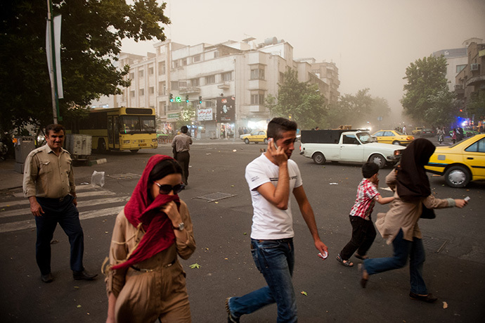 Iranians walk amidst dust as a sandstorm engulfs the capital Tehran on June 02, 2014. (AFP Photo / ISNA / Hamidreza Dastjerdi)
