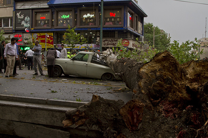The trunk of a tree lies over a smashed vehicle following a sandstorm and record winds in Tehran on June 02, 2014. (AFP Photo / Str / Fars News)