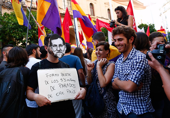 "A man wearing a mask depicting Spanish Prime Minister Mariano Rajoy holds a placard which reads, ""I am part of the 5.5 million unemployed in this country"" during a protest against the Spanish monarchy in the Andalusian capital of Seville, southern Spain June 2, 2014. (Reuters / Marcelo del Pozo)"