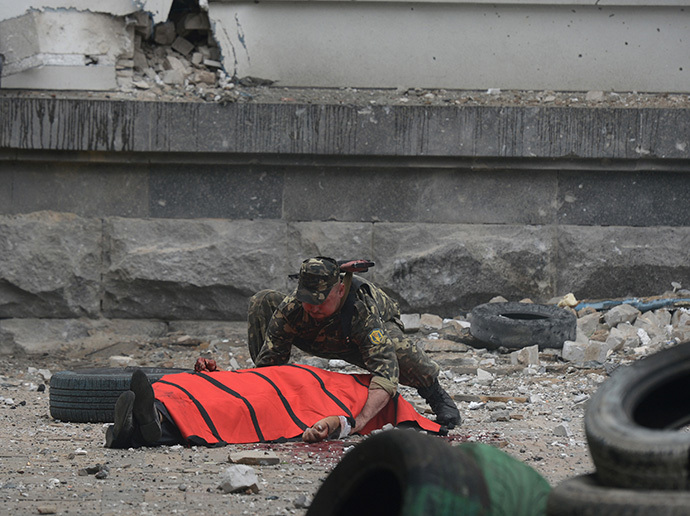 A member of the local self-defense forces covers the body of a person killed during the air attack on the building of Lugansk regional administration by Ukrainian air force. (RIA Novosti / Evgeny Biyatov)
