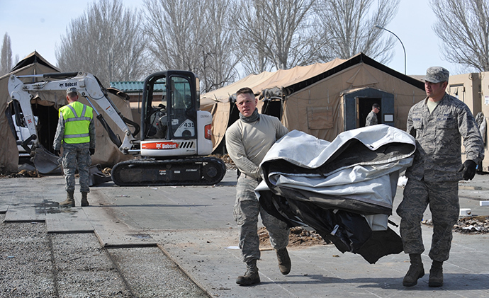 US servicemen carry a tent as they dismantle the tent camp at the US transit center in Manas, 30 kilometers outside Kyrgyzstan's capital Bishkek on March 6, 2014 (AFP Photo / Vyacheslav Oseledko)