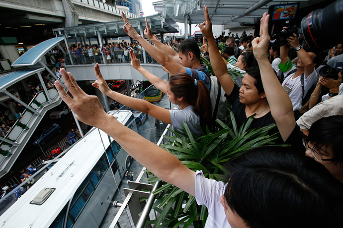 Protesters against military rule gesture by holding up their three middle fingers in the air, during a brief demonstration at a shopping mall in Bangkok June 1, 2014 (Reuters / Erik De Castro)