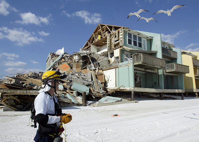 Juan Baquero of Central Florida Urban Search and Rescue Task Force 4 stands in front of a building, which was damaged by Hurricane Ivan, in Naverre Beach, Florida in this September 17, 2004, file photo (Reuters / Rick Wilking)